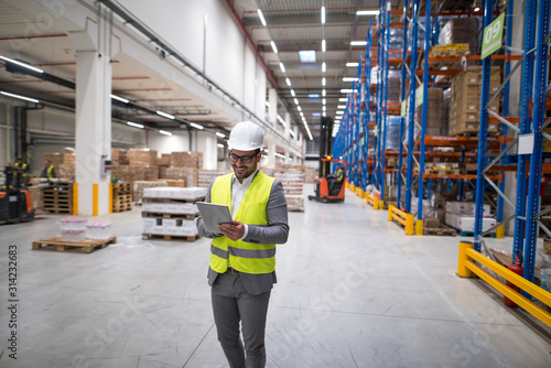 Fototapeta Warehouse manager walking through large storage area and holding tablet while forklift operating in background. obraz