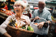 Leinwanddruck Bild - Mature couple shopping vegetables and fruits on the market. Healthy diet.