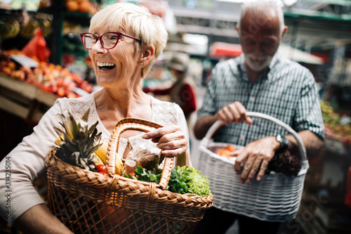 Fototapeta Mature couple shopping vegetables and fruits on the market. Healthy diet. obraz