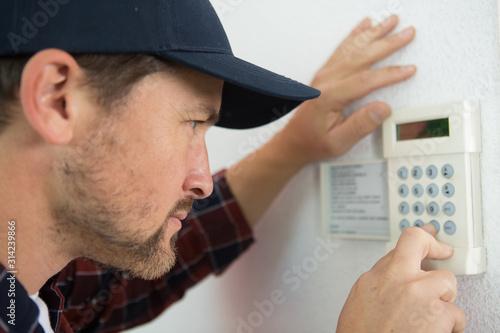 Photo a male technician repairing intercom