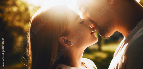 Fototapeta Close up portrait of a lovely young couple smiling before kissing against sunset with closed eyes outdoor in the park while dating. obraz