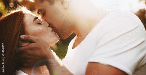 Portrait of a amazing young red haired woman kissing with her boyfriend with closed eyes against sunrise while man is touching her face Tableau sur Toile