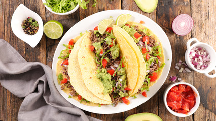 Fototapetatacos with guacamole, beef, tomato and cheese- tortilla bread