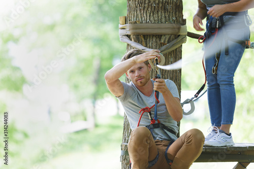 Fotomural portrait of man attaching harness to zip wire around tree