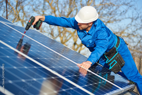 Photo Man worker in blue suit and protective helmet installing solar photovoltaic panel system using screwdriver