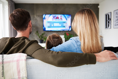 Photo Rear view of family watching tv in living room