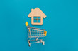 canvas print picture - Small supermarket cart for shopping toy wooden house on blue color paper flat lay background. Mortgage property insurance buy dream home shopping sale rent concept
