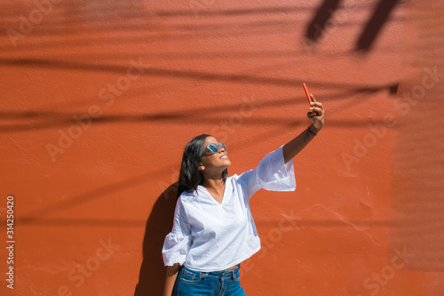 Fotomural  beautiful African-American young woman selfie in the city