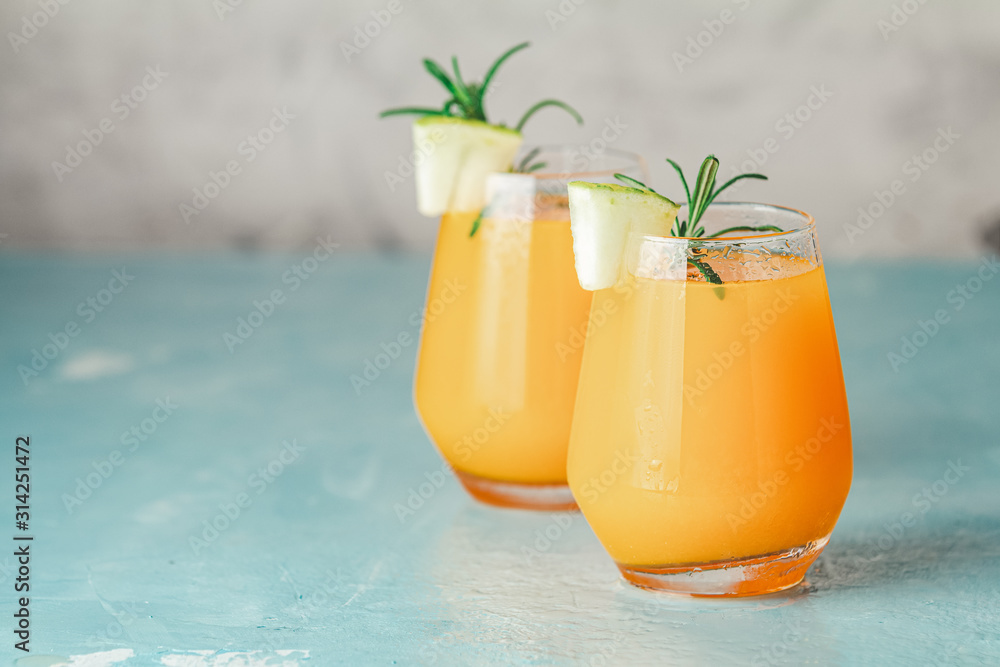 Fototapeta Yellow orange cocktail with melon and mint in glass on blue concrete background, close up. Summer drinks and alcoholic cocktails. Alcoholic or detox cocktail