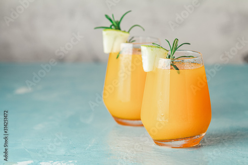 Fototapeta Yellow orange cocktail with melon and mint in glass on blue concrete background, close up. Summer drinks and alcoholic cocktails. Alcoholic or detox cocktail obraz