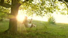 Young Girl Swinging On Swing On An Oak Branch In Sun. Dreams Of Flying. Happy Childhood Concept. Beautiful Girl In White Dress In Park. Teen Girl Enjoys Flight On Swing On A Summer Evening In Forest
