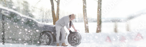 A man near a broken car on a winter day - 314254878