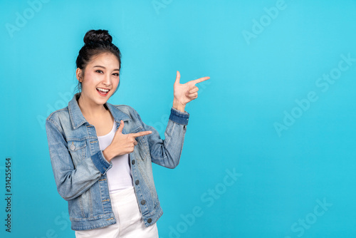 Leinwand Poster Happy asian woman feeling happiness and standing pointing hands to copyspace on blue background