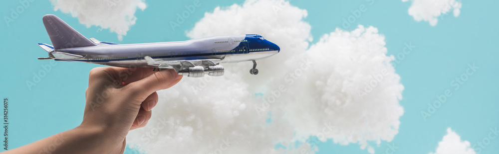 Fototapeta cropped view of woman playing with toy plane among white fluffy clouds made of cotton wool isolated on blue, panoramic shot
