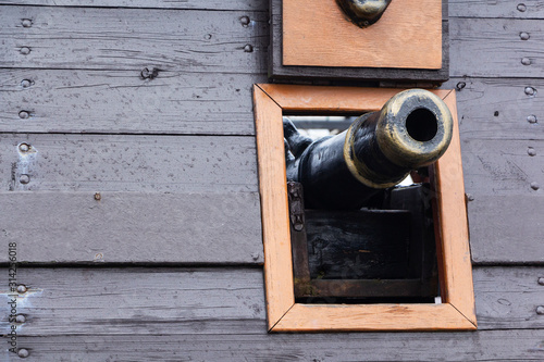 An old pirate sailing wooden boat with open gun compartments and canons Fototapeta