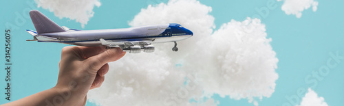 obraz PCV cropped view of woman playing with toy plane among white fluffy clouds made of cotton wool isolated on blue, panoramic shot