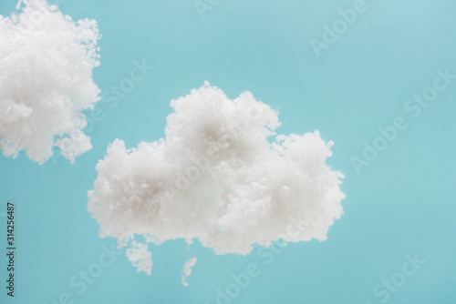 white fluffy clouds made of cotton wool isolated on blue background Fototapet