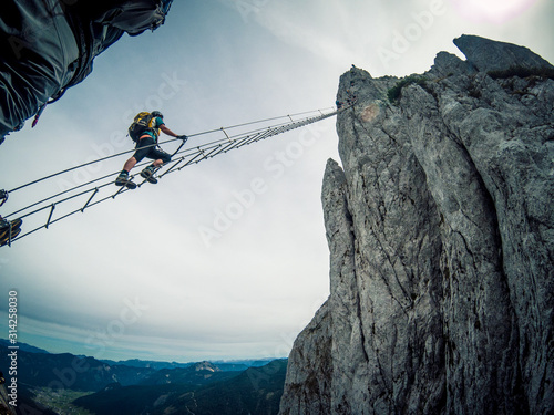 Obraz Via ferrata Intersport Klettersteig - climbing up a long ladder - fototapety do salonu