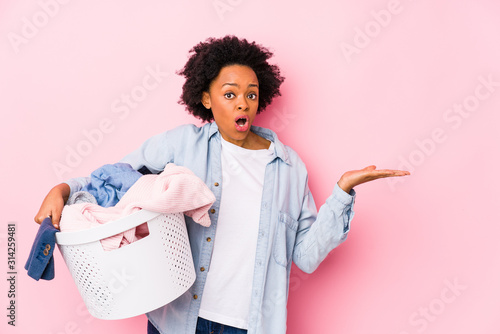 Fényképezés Middle age african american woman doing laundry isolated impressed holding copy space on palm