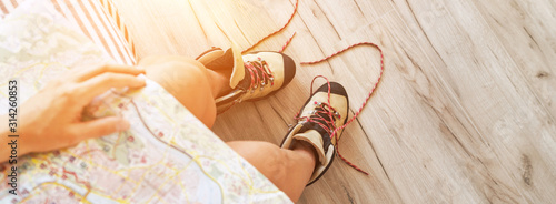 Fototapeta Young female inspecting a city map resting on the bed with untied trekking boots on wooden floor obraz
