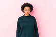 Middle aged african american woman against a pink background isolated blows cheeks, has tired expression. Facial expression concept.