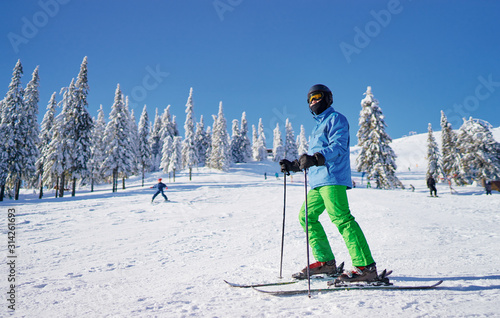 Fotografering Happy young man skier enjoying sunny weather in snowy mountains