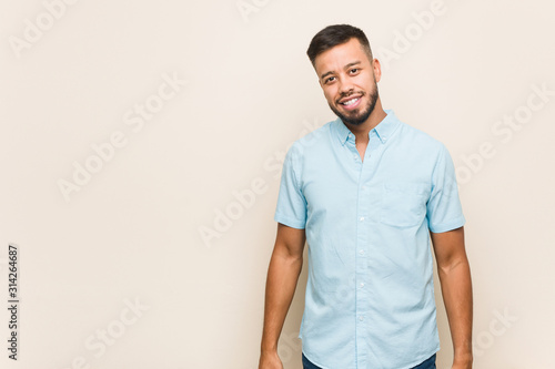 Obraz Young south-asian man stretching arms, relaxed position. - fototapety do salonu