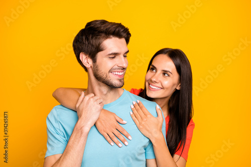 Obraz Photo of two adorable guy lady people couple hugging piggyback charming looking eyes hold arms wear casual blue orange t-shirts isolated yellow color background - fototapety do salonu
