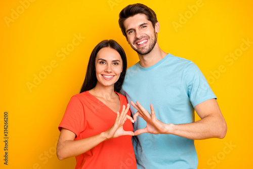 Obraz Photo of amazing two people guy lady celebrating valentine day holding fingers heart figure shape wear casual blue orange t-shirts isolated yellow color background - fototapety do salonu