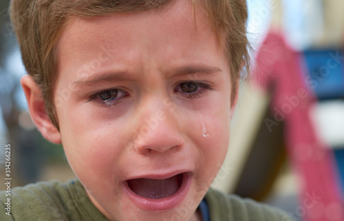 Photo afflicted kid with the face of pain and despair