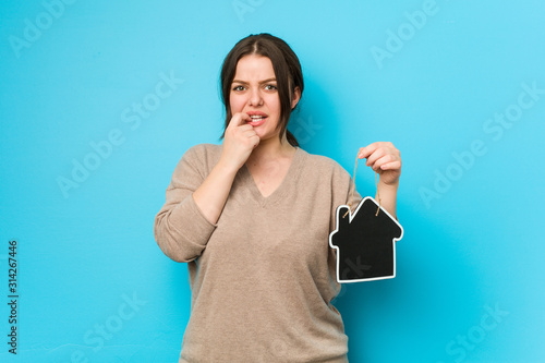 Photo Young plus size curvy woman holding a home icon biting fingernails, nervous and very anxious
