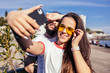 Charming young couple beautiful girl and charming man take a selfie on the phone while on vacation at sea. Honeymoon travel concept
