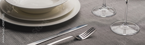 Serving plates with cutlery and wine glasses on grey cloth, panoramic shot