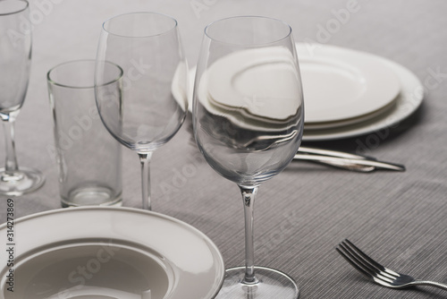 Serving dishware with glasses on grey tablecloth