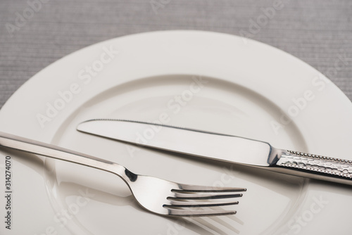 Close up view of cutlery on empty plate on grey surface