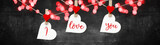 I love you, Valentine's Day background banner panorama - White heart hang on wooden clothes pegs with wooden heart on a string isolated on black concrete stone wall, with space for text