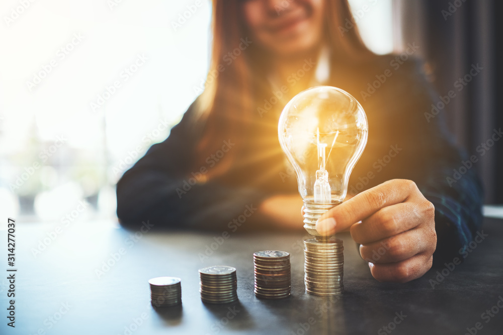 Fototapeta Businesswoman holding and putting lightbulb on coins stack on table for saving energy and money concept