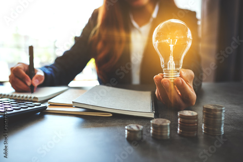 Obraz Businesswoman holding a lightbulb while taking note on notebook with coins stack on table, saving energy and money concept - fototapety do salonu