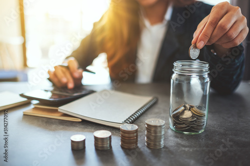 Obraz Closeup image of a businesswoman stacking and putting coins in a glass jar - fototapety do salonu