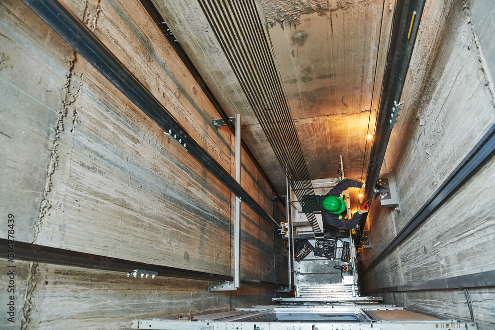 Obraz lift machinist repairing elevator in lift shaft fototapeta, plakat