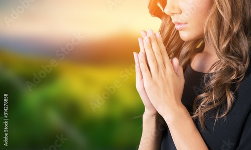 Fotografie, Obraz A young beautiful  girl praying on blurs background