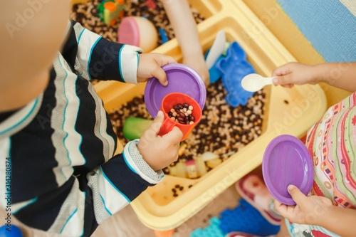 Fototapeta Children play educational games with a sensory bin in kindergarten obraz