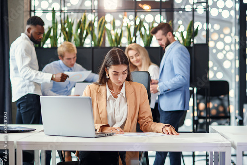 Obraz na plátně  Pretty female office manager sits at her working table and uses two laptops in o