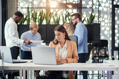 Photo  Pretty female office manager sits at her working table and uses two laptops in o