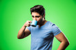 Leinwandbild Motiv Indian man with tea / coffee cup drinking or holding, standing isolated over green background