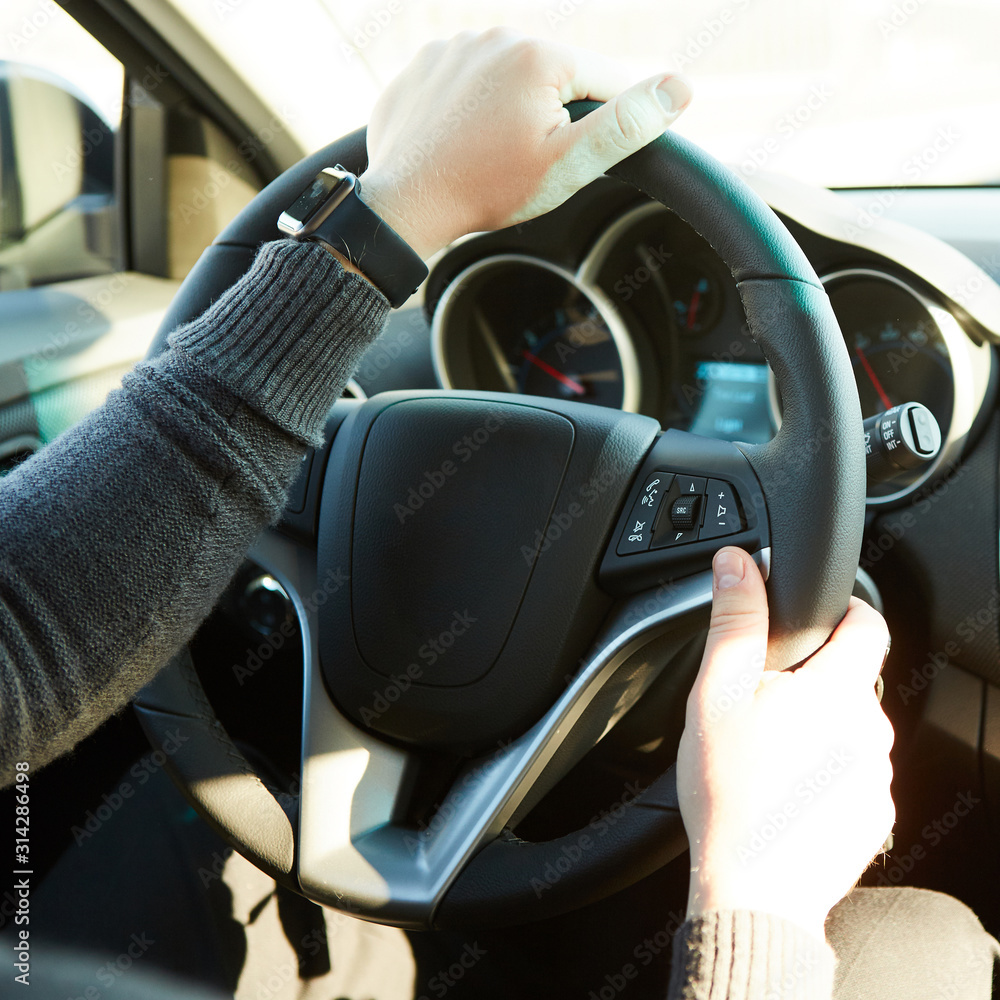 Fototapeta Close-up Of A Man Hands Holding Steering Wheel While Driving Car