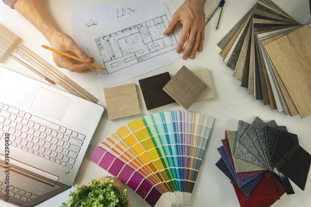 Fototapeta designer working in office doing furniture and flooring material selection from samples for home interior design project. top view