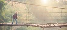 Asian Tourist Man Walking On The Old And Broken Wood Bridge
