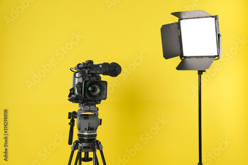 Fototapeta Professional video camera and lighting equipment on yellow background