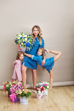 Happy Family Mother And Two Beautiful Girls Daughters On Holiday In Flowers Together On Isolated Background